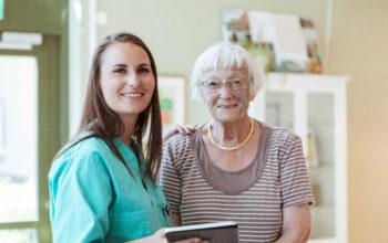 Portrait of smiling senior woman and nurse with digital tablet at home